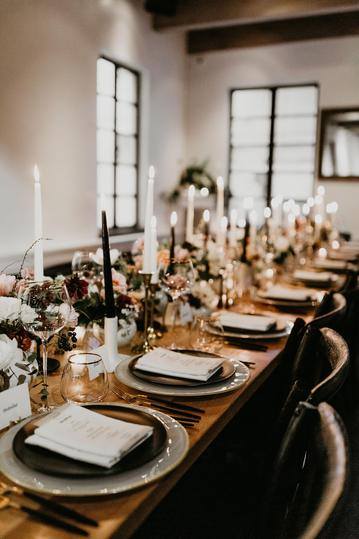Intimate, moody long farm table dinner with lots of floral arrangements and taper candles nyc