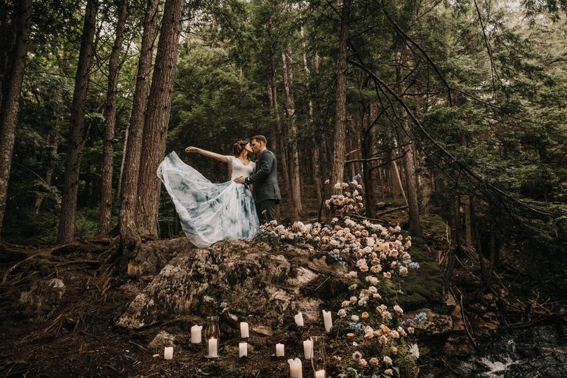 Married Couple in mountain cliffside next to a waterfall with pops of blooms growing around them with scattered lit candles