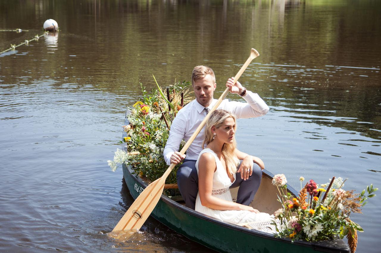 A young woman bride and her husband riding in a canoe full of flowers holding a beautiful summer bouquet of flowers for her wedding elopement in the hudson valley new york on a private lake