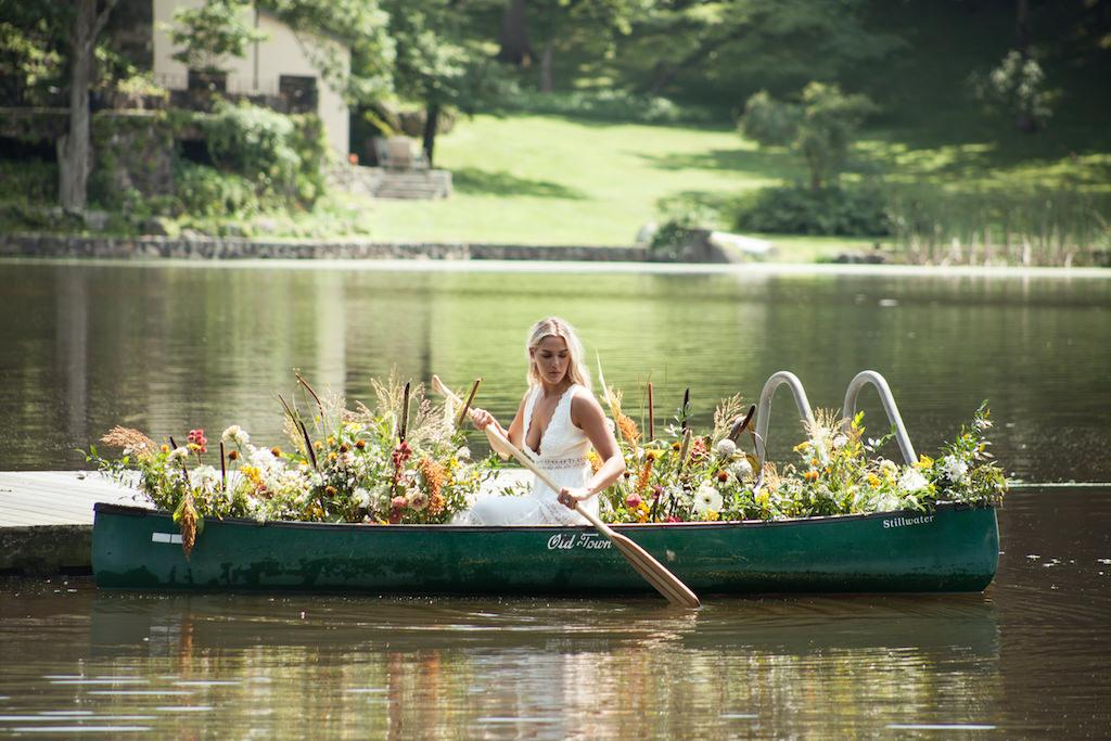 A young woman bride riding in a canoe full of flowers to her elopement in the hudson valley new york