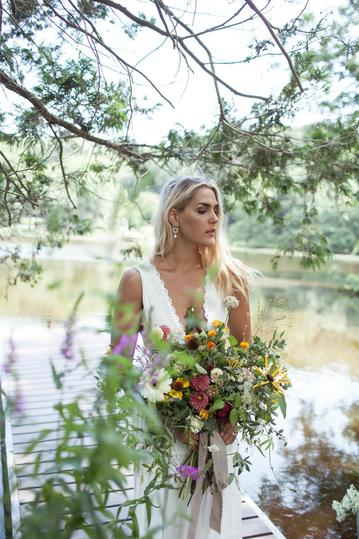 A young woman bride holding a beautiful summer bouquet of flowers for her wedding elopement in the hudson valley new york on a private lake