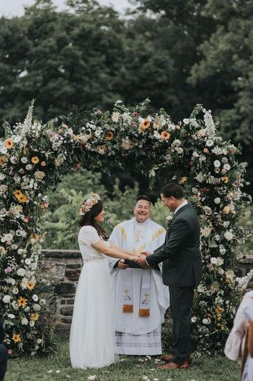 A young couple holding hands and exchanging vows at their wedding at Stone Barns Blue Hill under a large wildflower arch