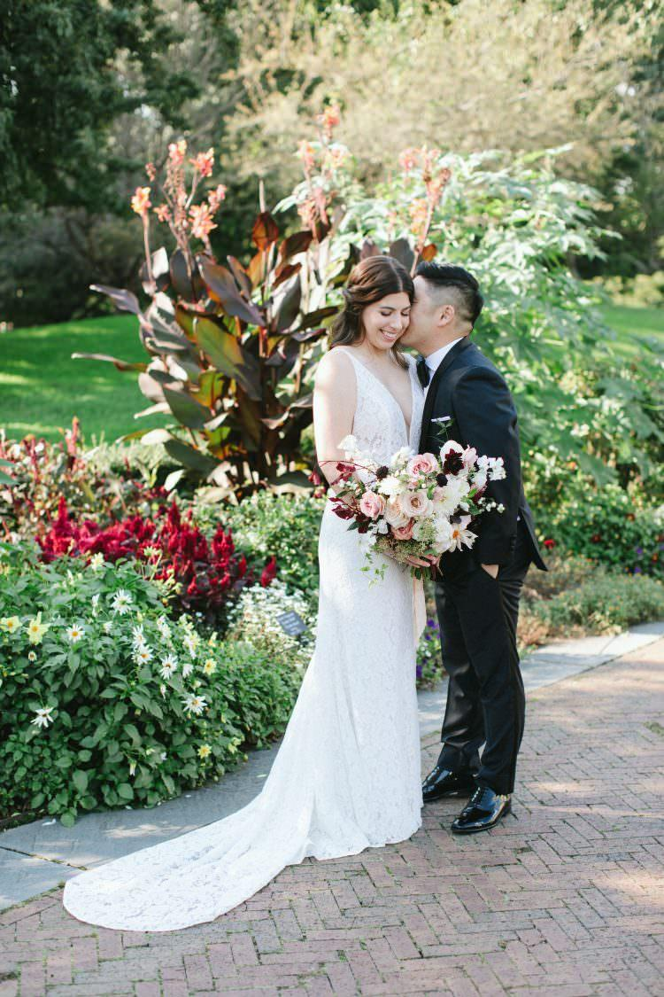 a young married couple holding one another at their wedding at the Brooklyn Botanical Garden in New York