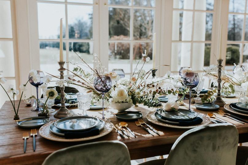 A soft, delicate light blue and white wedding tablescape at a wedding in a mansion