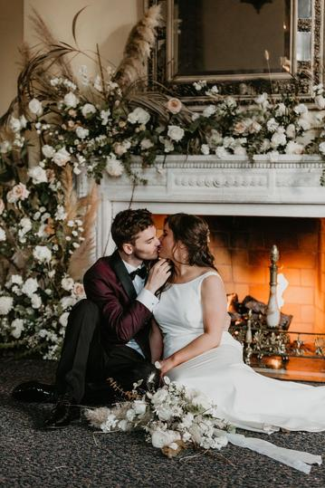 young married couple caressing one another sitting in front of a lit fireplace decorated with lots of blooms, greenery, and pampas grass