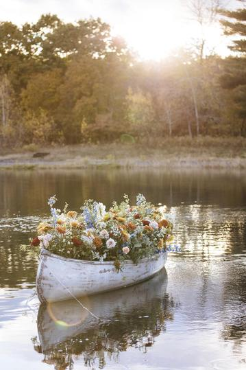 A large colorful floral installation in a canoe on a pond for a creative retreat in upstate new york at gather greene with the brands shopbop and levis